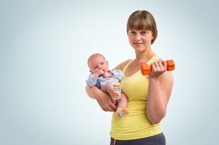 Bonne jeune femme renforce avec haltère après l'accouchement et détient le nouveau-né