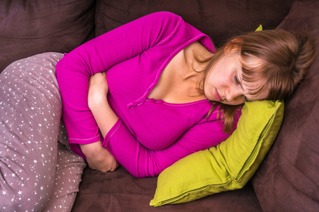 Woman lying on sofa and holding hands on her stomach at home