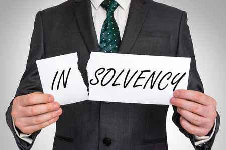 Businessman tearing paper with insolvency word, he makes solvency word - business idea concept