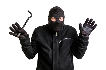 Arrested masked thief in balaclava with crowbar and raised arms isolated on white background