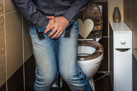 Man with hands holding his crotch, he wants to pee in restroom - urinary incontinence concept Standard-Bild