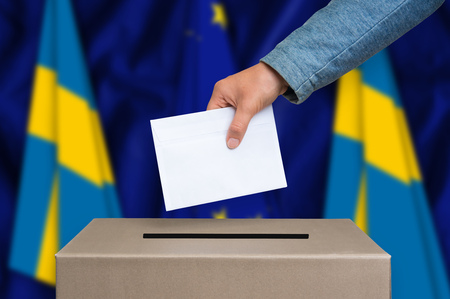 Election in Sweden. The hand of woman putting her vote in the ballot box. Sweden and European Union flags on background. Stock Photo