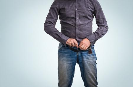 男は青い背景におもらしした後彼のズボンをジップアップします。 写真素材