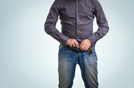 Man zip his pants up after peeing on blue background
