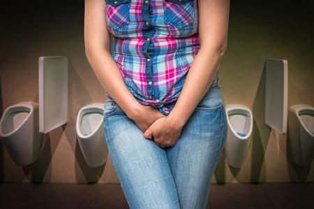Mujer con las manos sosteniendo su entrepierna en el baño público de los hombres, ella quiere orinar - concepto de la incontinencia urinaria Foto de archivo