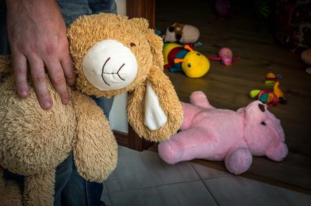 子供部屋に立って、かわいいおもちゃを子供に提供している小児性愛者の画像