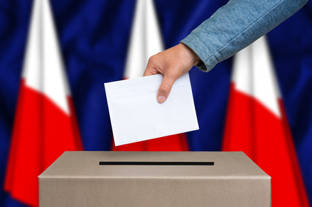 Election in Poland. The hand of woman putting her vote in the ballot box. Polish flags on background.