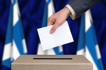 scottish parliament: Election in Scotland. The hand of man putting his vote in the ballot box. Scottish flags on background.