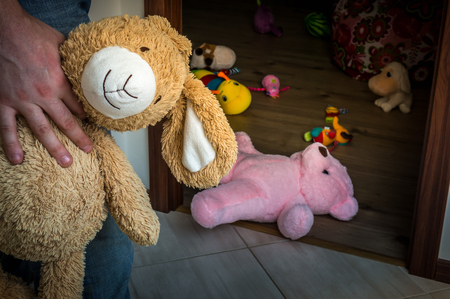 pedophilia: Picture of pedophile standing in the child room and offering cuddly toy to child