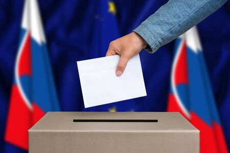 Election in Slovakia. The hand of woman putting her vote in the ballot box. Slovak and European Union flags on background. Stock Photo