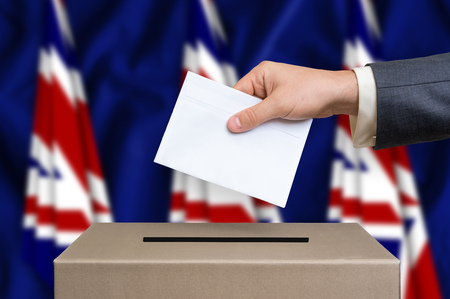 Election in United Kingdom. The hand of man putting his vote in the ballot box. United Kingdom flags on background.