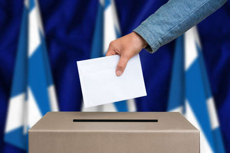 scottish parliament: Election in Scotland. The hand of woman putting her vote in the ballot box. Scottish flags on background. Stock Photo