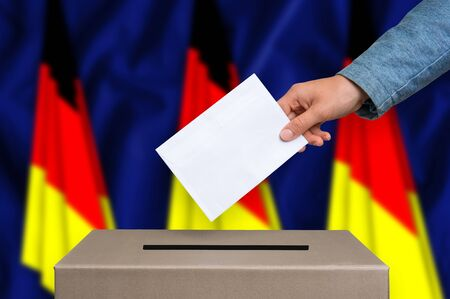 Election in Germany. The hand of woman putting her vote in the ballot box. German flags on background. Stock Photo