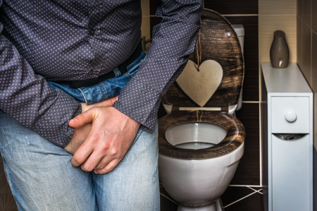 Man with hands holding his crotch, he wants to pee in restroom - urinary incontinence concept Stockfoto