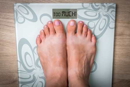 Womans feet on a scale with word TOO MUCH! - obesity concept