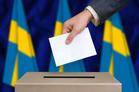 Election in Sweden. The hand of man putting his vote in the ballot box. Swedish flags on background.