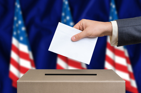 Election in United States of America. The hand of man putting his vote in the ballot box. American flags on background.