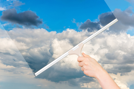 Cleaning window with rubber squeegee and cleaning the sky Stock Photo