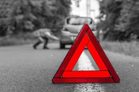 Driver in reflective vest changing tire and red triangle warning sign - black and white concept