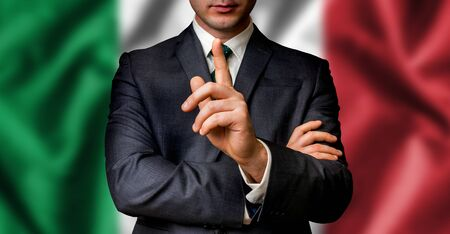 Italian candidate speaks to the people crowd with one finger on lips - election in Italy