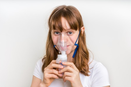 Woman with asthma symptoms making inhalation with mask - medical inhalation therapy