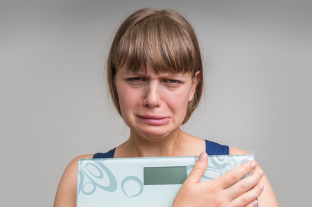 Frustrated overweight woman with scales - diet and obesity concept