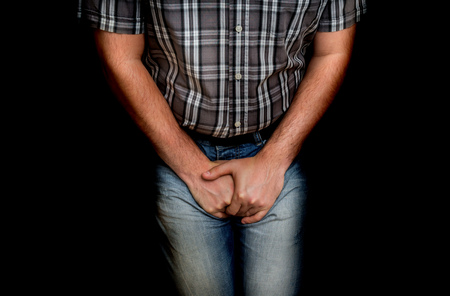 Man with hands holding his crotch, he wants to pee - urinary incontinence concept Standard-Bild