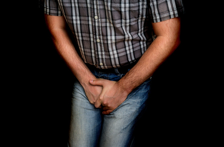 Man with hands holding his crotch, he wants to pee - urinary incontinence concept Stockfoto