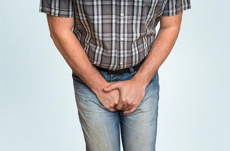 Hombre con las manos sosteniendo su entrepierna, quiere orinar - concepto de incontinencia urinaria Foto de archivo