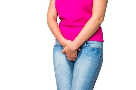 Mujer con las manos sosteniendo su entrepierna, ella quiere orinar - concepto de la incontinencia urinaria