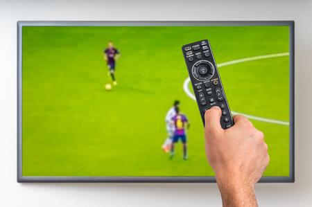 男はテレビ、テレビのリモコンを手に保持でサッカーを見ています。