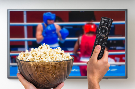 Man is watching boxing match on TV and holding tv remote controller and popcorn in hands