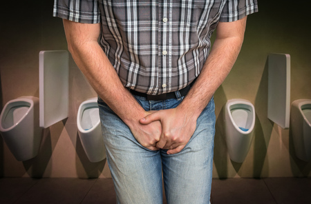 Man with hands holding his crotch, he wants to pee in restroom - urinary incontinence concept Stock Photo