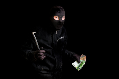 Masked thief in balaclava with crowbar isolated on black background