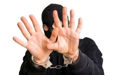 handcuffs: Masked thief in handcuffs covering face isolated on white background