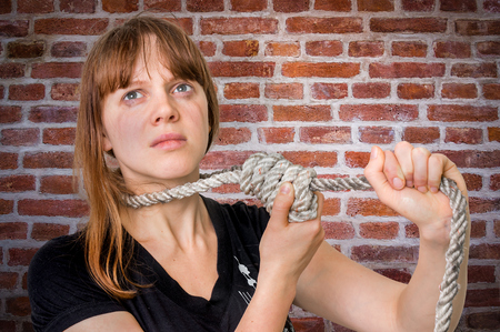 Depressed woman with a noose around her neck - suicide concept