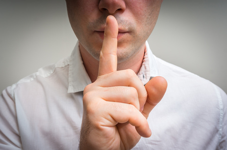 Attractive man with finger on lips making silence gesture. Shh!!!