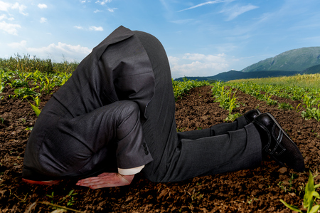 Unsuccessful businessman burying his head in the ground Stock Photo