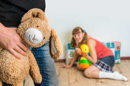 Picture of pedophile standing in the child room and offering cuddly toy to young girl
