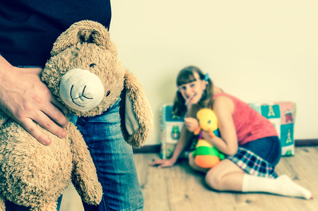 Picture of pedophile standing in the child room and offering cuddly toy to young girl - retro style