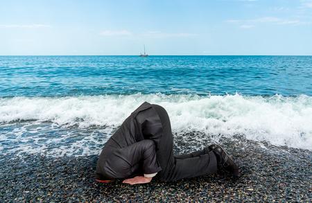 Hombre de negocios sin éxito, enterrando la cabeza en el suelo