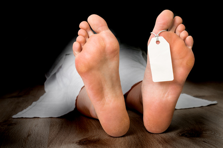 Dead woman lying on the floor under white cloth with blank tag on feet Stock Photo