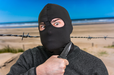 Terrorist threatening western countries with knife - terrorism and hybrid warfare concept Stock Photo