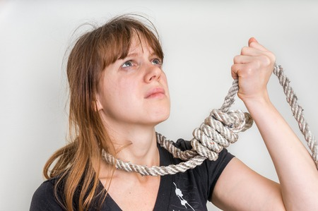 Depressed woman with a noose around her neck isolated on white - suicide concept