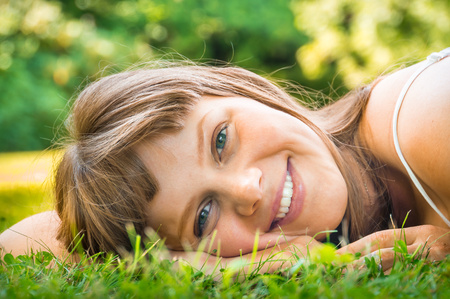 Young beautiful teenage girl lying on the green grass close-up