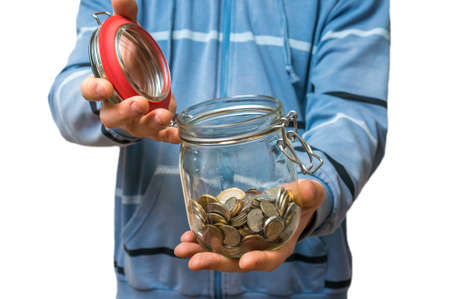 budgets: Man in blue sweatshirt holding money jar with coins isolated on white background