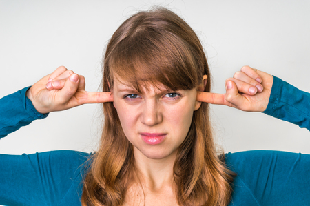 Woman closes ears with fingers to protect from loud noise isolated on white