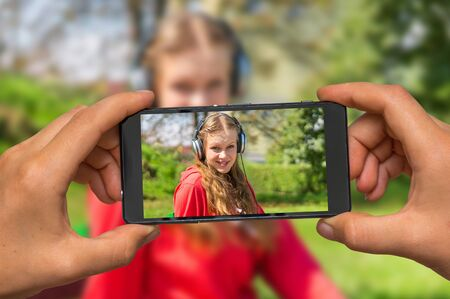 earpiece: Woman hands with mobile cell phone to take a photo of young lady listening to music and relaxing on a park bench
