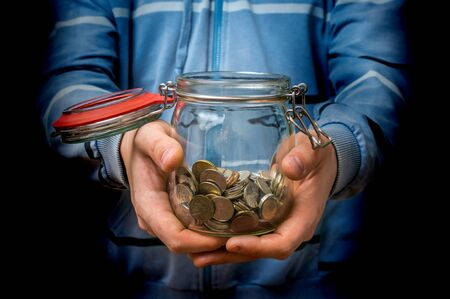 budgets: Man in blue sweatshirt holding money jar with coins isolated on black background