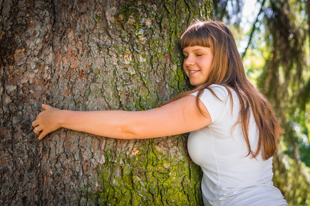 Happy young woman hugging a tree in the forest Stock Photo